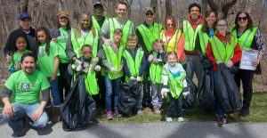 Volunteers wearing yellow vests collect trash near Doan Brook.