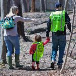 Volunteers wearing yellow vests collect trash near Doan Brook.