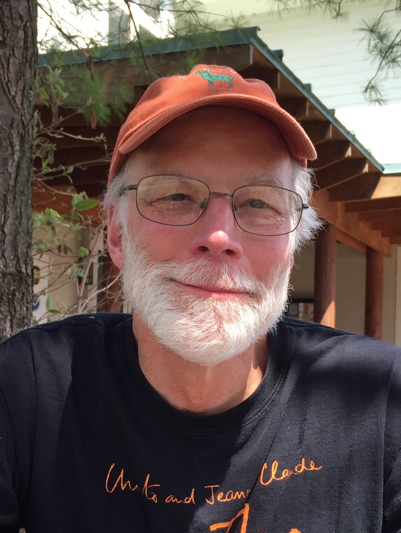 John Barber wearing an orange baseball cap and black shirt with orange writing.